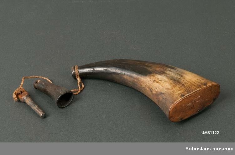 Kruthorn tillverkat av ett horn av får med oval botten. Hornet är ljust med svart topp. I bottnen pluggat med en träplatta, i smala änden med en träplugg som sitter i ett vidhängande snöre, knutet om hornet. Mynningen dekorskuren. Ett mått tillika ett extra lock som skydd för kruthornets mynning i form av en svart horntopp hänger i ett snöre. Kruthornet innehåller ett grövre krut. 20 juli 2011: Efter rekommendation kring förvaring gjord av Försvarets materielverk och Totalförsvarets forskningsinstitut vid besök på Bohusläns museum den 12 mars 2008 så har vi beslutat att överlämna krut och ammunition till vapenhandeln för destruktion. Gäller för UM25921 (innehåll i förpackning), UM25928 (11 laddade patroner) samt UM31122 (innehåll i kruthorn). Se bilaga till UM25928 i bilagepärm.  Använt av Carl Gustaf Bernhardson och hans far vid sjöfågeljakt.  Samhör med gevär UM31151-UM31152, övriga jakttillbehör: UM31153 - UM31156. Bernhardson skildrar sjöfågeljakten i många av sina målningar.  För ytterligare upplysningar om Carl Gustaf Bernhardson samt om förvärvet, se UM31100.  Litteratur: Nylén, Anna-Maja, Hemslöjd, Håkan Ohlssons förlag, Lund 1978, s. 396-401.