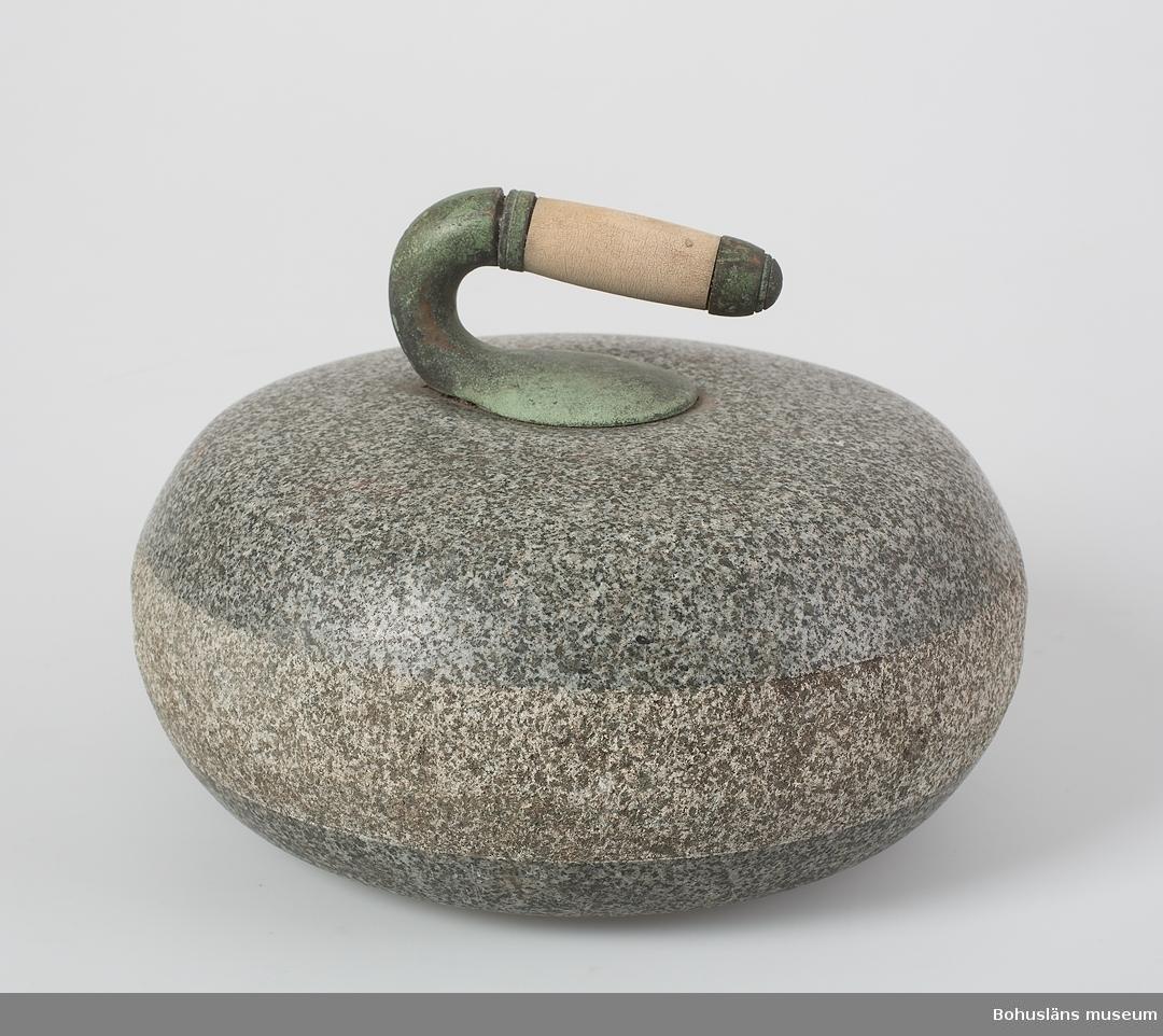 Cirkelrund curlingsten med böjd handtagsdel av dekorgjuten brons med grepp av trä. Stenen är mycket jämn med slätpolerad ovan- och underdel och med ett råslipat mellanparti, 5 cm högt, som löper runt hela stenen.  Handtaget är grönkorroderat och något stukat.