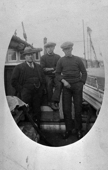 """Enl. tidigare noteringar: """"Besättningen ombord på motorskonerten """"Tore"""".  Fr v: Karl A Ögård, Gravarne. Harry Ferm, Bovallstrand och Jan Larsson, Bovallstrand. Repro av foto tillhörande Thore Ögård, Kungshamn""""."""
