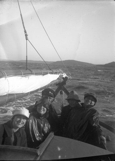 """Enl. text i blå bok: """"Personer i en sittbrunnen på en segelbåt."""" ::"""