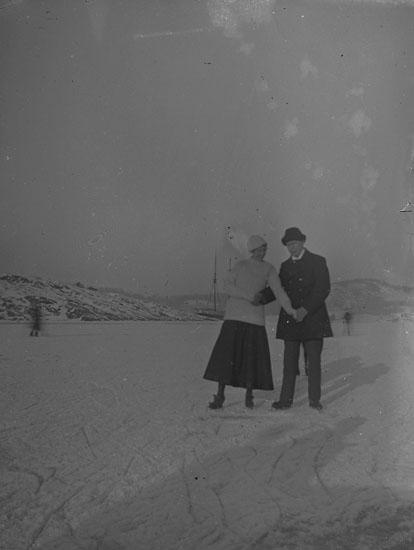 """Enl. text i blå bok: """"Par med skridskor på en fjord."""" ::"""