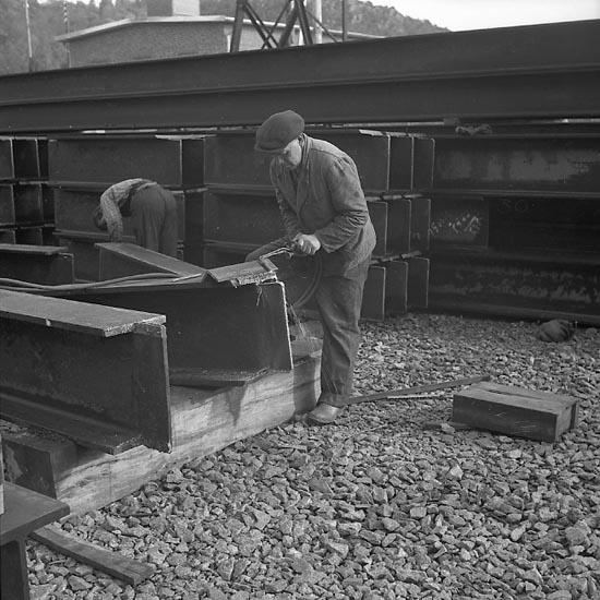 Varvsarbetare skär genom metall med handdriven skärbrännare
