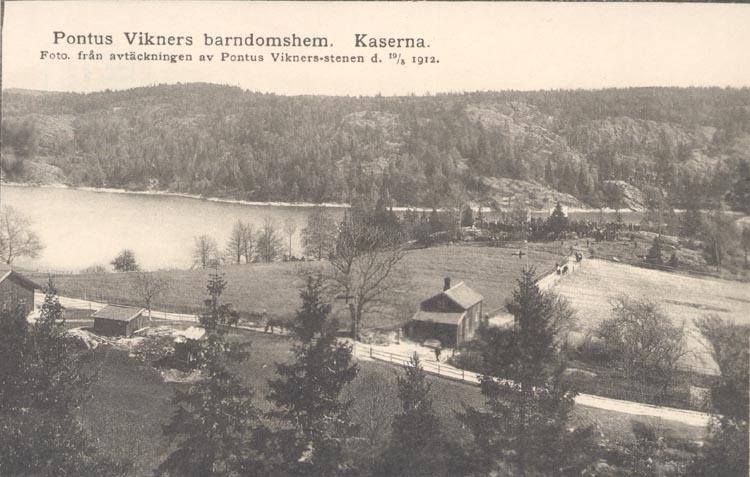 """Tryckt text på kortet: """"Pontus Wikners barndomshem. Kaserna. Foto. från avtäckningen av Pontus Wikners-stenen d. 19.5.12""""."""