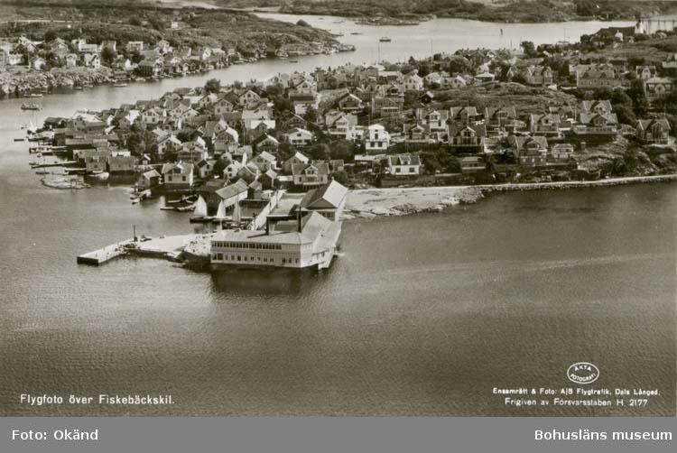 """Tryckt text på kortet: """"Flygfoto över Fiskebäckskil."""" """"Ensamrätt & Foto: A/B Flygtrafik, Dals Långed.""""  """"Förlag: Tyra Dahlqvists Eftr. Fiskebäckskil."""" Noterat på kortet: """"Fiskebäckskil Skaftö(landet). 6 Aug. 1954."""" """"F. och """"Kilen"""" fr. norr."""""""