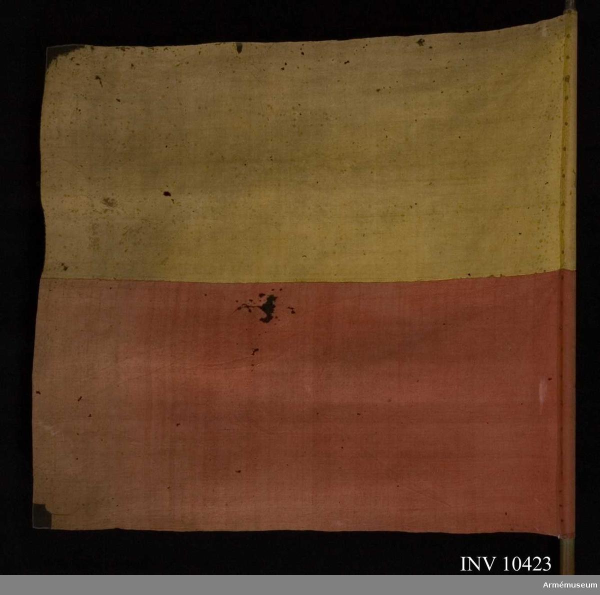 """Grupp B I.  Vidfäst lapp: """"Tillhör Edsvära kyrka"""" (Edsvära, socken i  Skånings härad, Skaraborgs län)  Duk av 4-skaftad ylleduk, delad; övre halvan gul, undre röd. Fäst med enkla spikar på läderband.Stång av omålad furu. Spets i ett med stångens trä, svartmålad rund knopp på konisk hals."""