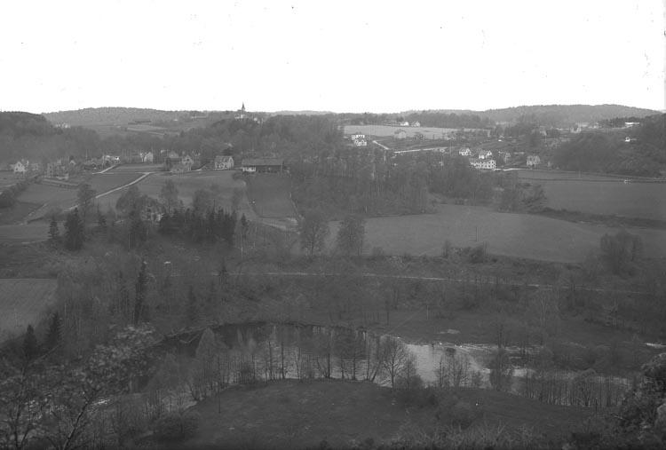 """Enligt fotografens noteringar: """"Älfven i förgrunden o. Foss Kyrka i bakgrunden i öf..? Munkedals samhälle."""""""