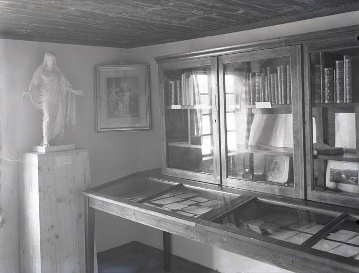 """""""1934. 24. Pontus Vikners barndomshem. Interiör af hans samlingar.""""  """"Kopia av Thorvaldsens Kristus. Dessa böcker och handskrifter förvaras numera på Bohusläns museum."""""""