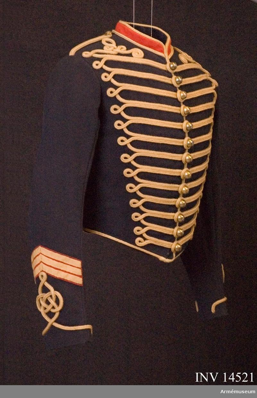 """Ridande artilleridivisionen, England. Grupp C I. Ännu i bruk 1913. Dolma av mörkblått kläde, kort, 45 cm lång (endast till midjan), enradig med 13 kullriga knappar. På bröstets bägge sidor finns 13 flätade dubbla guldsnören med öglor vid yttre sidorna. Vid axlarna, på bröstet, finns (på båda sidor) prydnadsbeläggningar av likadana snören samt vid slitsen på båda ryggsidorna beläggningar av samma material. På bröstets vänstra sida finns en hake för att hänga ägiljetter. Axelklaff av dubbla guldfärgade snören med knappar i större format. Foder av ylletyger, stoppade. Knappar av mässing, kullriga med drottningens krona och kanon ovanpå. Krage upprättstående med runda vinklar av rött kläde samt guldfärgade snören på nedre och övre kanten. Kragen försedd med hyska och hake samt fodrad med blått kläde. Uppslag runt omkring ärmarna av guldsnören med beläggning i form av en ungersk husarknut (på ungerska """"vitez-kötes""""). Ärmarnas utmärkelsetecken: På båda ärmar finns guldbroderat drottningens krona (tecken för högre underofficerare), kanon (tecken tillhörande artilleriet), sporre (tecken för """"bereiter""""), tre tränsar av guldgalon, 1 cm breda, alla tre i vinkelform och fastsydda vid en röd klädesbit i samma vinkelform (tecken för wachtmeister). Litteratur: Handbuch der Uniformkunde, Prof. R. Knötel, Hamburg 1937, sid 213: Artillerie. Ridande artilleri hade från år 1815 till första världskrigets början (1914) mörkblå dolma med röd krage och guldsnören på bröstet samt knutar på ärmuppslag av ungersk modell. Die Heere und Flotten der Gegenwart, Grossbritanien und Irland, G. von Zepelin 1897, Leipzig, sid 49: Uniformen för ridande artilleri bestod av kort mörkblå dolma med många gula snoddar på bröstet, ärmuppslag, krage och rygg. Sid. 192: (bild i färger) menigs ärmar med olika utmärkelsetecken. Tredje i första raden - Wachtmeister - ridande artilleri, detsamma för dolman. Sid 192: (titeln på eng.) """"Batteri-Sergeant-Major rider"""" - Batteri-Wachtmeiser-Bereiter (tillhör sjätte klas"""
