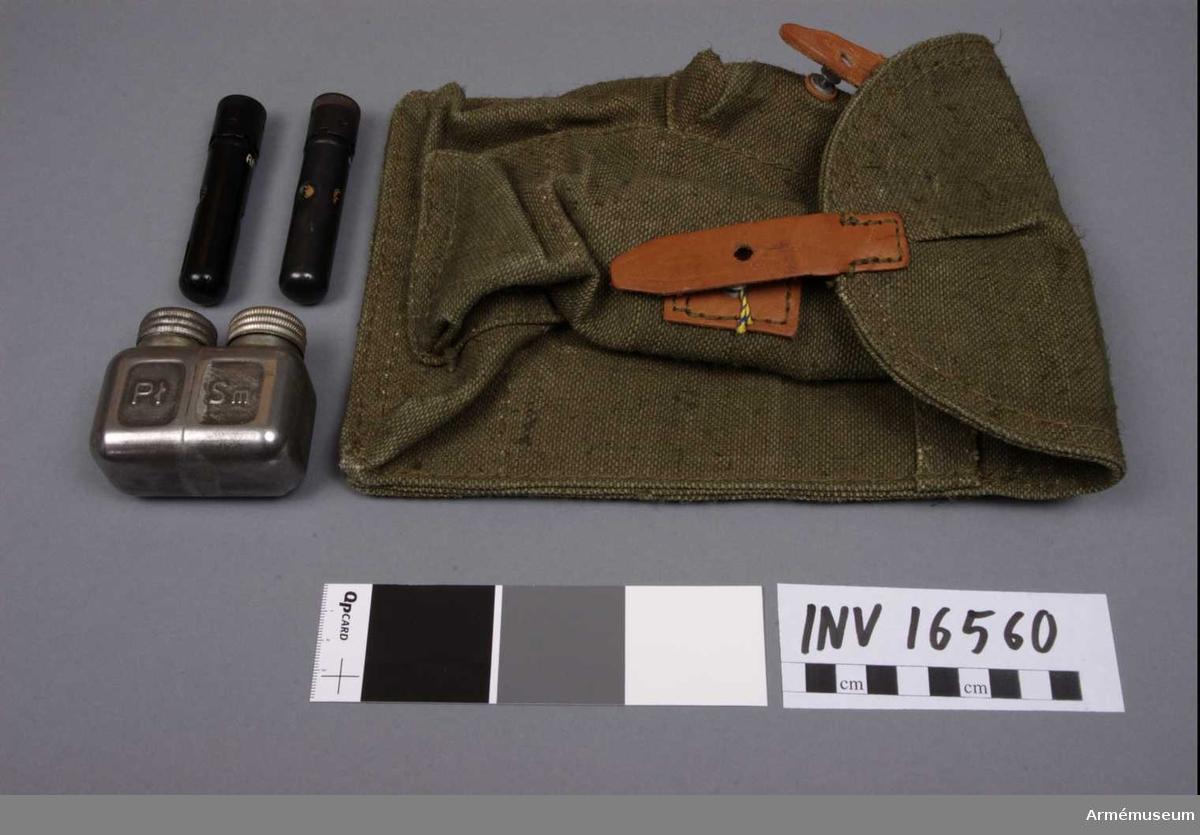 Väska t stångmagasin, Kalashnikov, Sovjet. Väska av väv för 3 st stångmagasin AKM, Kalashnikov, med rengöringstillbehör. Består av 4 delar.  1 väska av väv, märkt: Rek 1983. 1 oljedosa av järnplåt märkt: P SM, med 2 st skruvlock. 2 tillbehörsdosa av svartlackerad järnplåt. En dosa med 1 borstviskare, 1 läskända, 1 universalnyckel och 1 dosa. Den andra dosan har 1 borstviskare, 1 läskända, 1 don, 1 stift, 1 universalnyckel och 1 dosa.