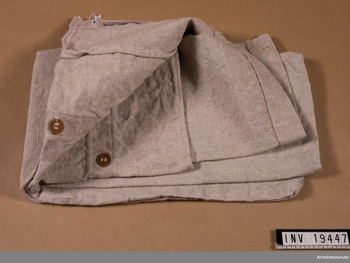 Sytt av naturfärgat linne. Sömmarna är vändsydda på tre sidor. Ena kortsidan är avsedd att vikas över och är försedd med fyra knapphål. På motsvarande kortsida finns knappar i trä.  Samhörande nr: AM.19445-8