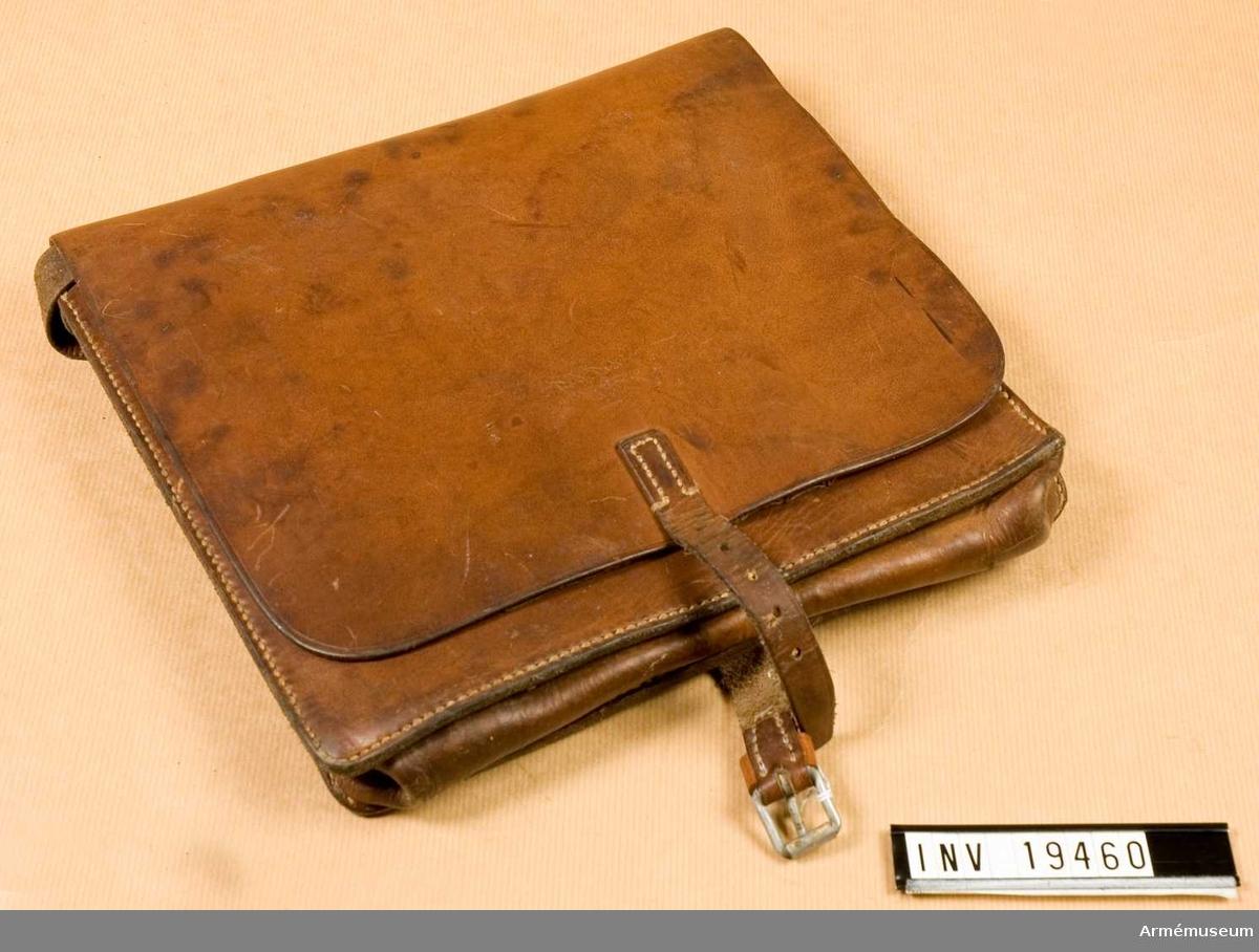 M 7083-001010-3. Av brunt läder med ställbar axelrem. Innehåller två stora fack och ett fastsytt etui för pennor och dylikt. Väskan knäpps med läderrem och sölja. Locket är stämplat med tre kronor.