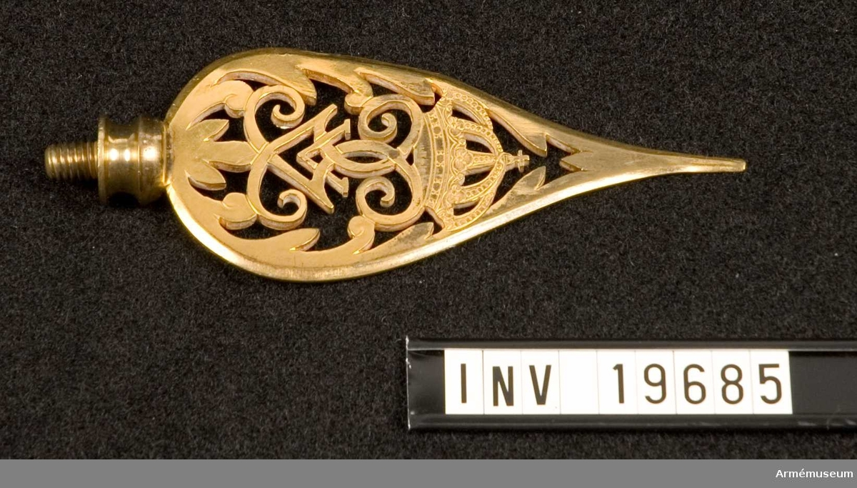 Spetsen är tillverkad av förgylld mässing. Den har Gustav V:s spegelmonogram under en kunglig krona inramat av ett bladverk som avslutas i en spets. Spetsen är försedd med skruv. Bladet tillhör standar AM 19684.  Samhörande nr AM 19684 - AM 19686, standar, spets, kordong.
