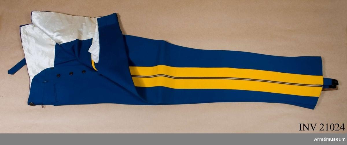"""Grupp C I. Ur uniform för överste vid Dragonregementet König Friedrich III 2. schlesiska, nr 8 VI Armékåren, Tyskland. Består av syrtut, vapenrock, ridbyxa, långbyxa, överrock, hjälm, mössa, skärp, kartusch, bandolär, axelklaffar, sabel med balja och portepé. Långbyxor av ljusblått kläde med gul passpoil och två gula revärer, b:40 mm. På framsidan tre fickor; två stora med små knappar samt en för klocka. Sprund med fem knappar, hyska och hake. Sex knappar för hängslen; spänntampp av kläde med  spännen av vit metall. Foder av vitt siden. Fållarna har hällor med mässingsknappar i mitten. Knapparna har påskriften """"J. Robrenth Berlin."""" LITT  Das Deutsche Heer. Zweiter Band (I) Kavallerie. Bild 79. Regementsuniformer i färg. Band I. Bild 62: Hällor och parad- byxor. Bekleidungs-vorschrift für Offiziere und Sanitätsoffiziere des König. Preuss. Heeres. Berlin 1899. Sida 64, 65 par. 81 C. Dragoner, paradbyxor. Beskrivning. Geschichte der Bekleidung und Ausrüstung der König. Preuss. Armée in den Jahren 1808 bis 1878. Berlin 1878. Sida 179, par. 996. Dessa långa blå paradbyxor infördes efter en dagorder av den 23 januari 1862 för dragonofficerare. Das Deutsche Reichsheer. Sida 80, 81. Reg:t, vars färg är citrongul, grundades efter en dagorder av den 10 maj 1860.Enl W Granberg."""