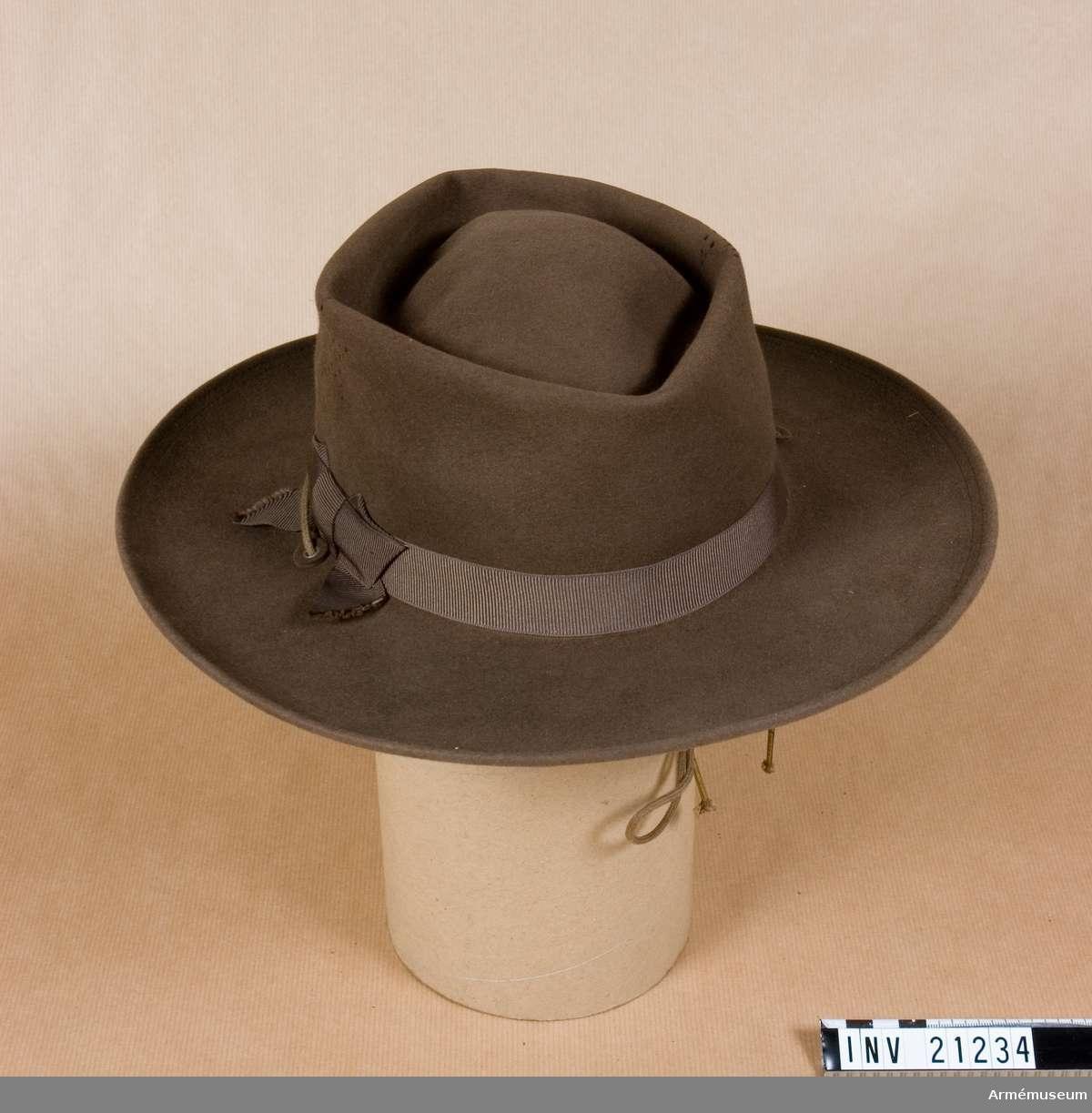 Grupp C I. Ur uniform för manskap vid infanteri, USA. Består av vapenrock, byxor, bälte, hatt, sporrar, damasker, revolverfodral. Civil modell. Av filt i kakifärg. Fyra lufthål på fyra sidor. Silkesband, kakifärgat, b:20 mm, runt om. Svettrem av brunt läder. På framsidan två snören för att sätta fast hatten.
