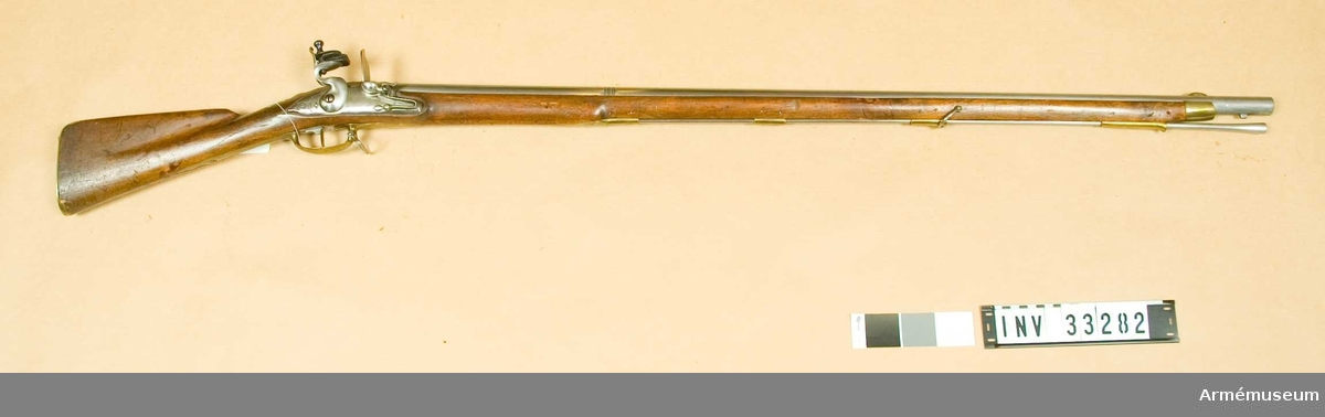 """Grupp E II. Med flintlås. Varbygelns längd med främre-bakre arm: 308 mm. Låsets l:164 mm, sidbleckets l:150 mm. Märkning på pipan: """"CA"""", ett tecken med likhet av en kvartsnot, """"74.R C.A.N.A5""""; på låset """"GR Georg"""" med kunglig krona och """"PM"""" inom en fyrkant. GR=Georg Rex. Beslag av mässing. Stock av valnöt. Omnämnt första gången i 1889 års inventarium. Ankomstnotering saknas. Översändes genom friherre Sprengtportens försorg till Kungliga Krigskollegium 1790."""