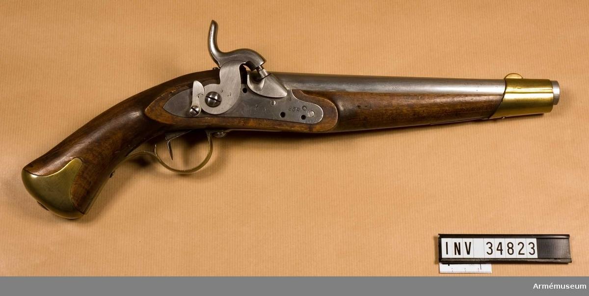 """Grupp E III b.  Projekt, sannolikt av Callerström på 1830-talet. Vapnet är ursprungligen en i Carl Gustafs stads gevärfaktori år 1837 tillverkad flankörpistol med flintlås m/1820, (se AM 1932:16812), vars lås ändrats till slaglås. Pipan är blank. Baktill på högra platten har fastlötts en stor, med kraftig eldskärm försedd snäcka. Den sistnämnda skjuter på utsidan ut 0,5 cm utanför låsblecket. I övrigt är pipan ej förändrad. På pipans undersida står 238. På svansskruvsstjärtens H sida är inslaget siffan 5 samt på densammas undre sida 238.  Låset har invändigt icke omändrats. Hålen för eldstålsfjäderas skruv, för eldstålsfjäders tapp samt för pannskruven har ej utfyllts. Hanens hals och platt har rektangulärt tvärsnitt. Hanens tumgrepp är ej refflat och urholkningen i hanens slagarm har ej springa framtill. Varhaken är baktill slät. På låsbleckets utsida finnes ett krönt C, siffran 5 och 238. På hanens utsida är siffran 5 inslagen tre gången. På bleckets insida finnas SG och 1837 angivna. Alla låsets skruvar är märkta med siffran 2. I halvspänn står låset högt, men i hakspänn står hanens slagyta blott obetydligt över knallhattstappen.  Stock och beslag är oförändrade m/1820. På stockens vänstra sida bakom sidblecket står 238 och på stocken undersida till vänster om varbygelns främre arm är ett G inslaget. På kolvänden under kolvkappan är på träet siffran 5 inslagen flera gånger. På utsidan av sidblecket samt på varbygels arm är siffran 5 inslagen två gånger på vardera stället. På insidan av samtliga mässingsbeslag är ett B inslaget. På anslagsjärnet är siffran 5 insagen flera gånger och de skruvar vilka fasthåller anslagsjärnet är numrerade från och med 29 till och med 32. I reversalen från Carl Gustafs stads gevärsfaktori kallas pistolen för m/1850. I Artillerimuseum kallades vapnet 1906 """"Flankörpistol med slaglås 1850-talet, ändrad från flintlås"""". Senare omdöptes den till """"Flankörpistol med slaglås, förändringsmodell 1857 från pistol med flintlås m/1820, för K. Smål"""