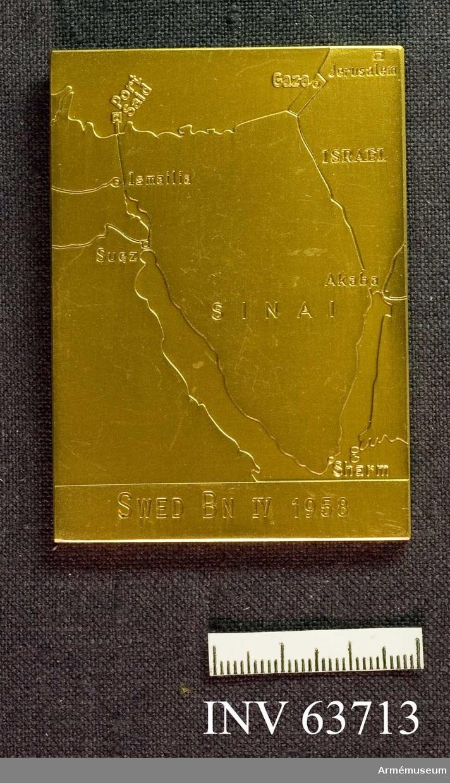 """Grupp M II. Plakett i guld. Åtsidan: """"Svenska FN-BATALJONEN"""", under sköld med tre kronor och kunglig krona. Frånsidan: """"SWED BN IV 1958"""" och karta över Sinai-halvön. Tillverkare: Sporrong & Co."""