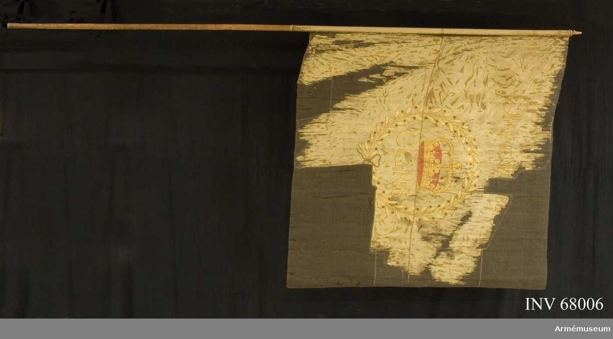 Duk: Enkel, tillverkad av gul sidentaft, sydd av två horisontella våder. Duken fäst vid stången med en rad tennlikor på ett gult band. Bandet virat om stången ytterligare en bit.  Dekor:  Målat omvänt lika på båda sidor Carl X Gustavs initialer i guld. Över den en gyllene sluten krona med låga byglar och rött inner och ytterfoder. Det hela omges av en liten krans bildad av två gyllene lagerkvistar med omväxlande bär och blad, nedtill hopknuten med en rosett. Bladverk i guld, bär och rosett, mörka, eventuellt i silver.   Stång: Tillverkad av omålad furu. Tecken inristade på stången.