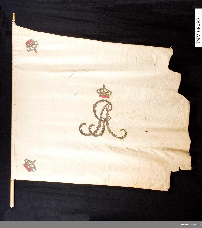 Duk: Tillverkad av enkel vit sidenkypert, sydd av tre horisontella våder. Duken kantad med ett vitt mönstervävt band. Fäst med stift vid stången.  Dekor: Broderad i dubbelsidig plattsöm i metalltråd. Gustav IV Adolfs namnchiffer (GA), omvänt lika på båda sidor. Krönt av en sluten krona med foder i rött silke och stenar i olikfärgat silke. I hörnen liknande kronor.  Stång: Tillverkad av vitmålad furu. Holk av förgylld mässing. Saknar spets.