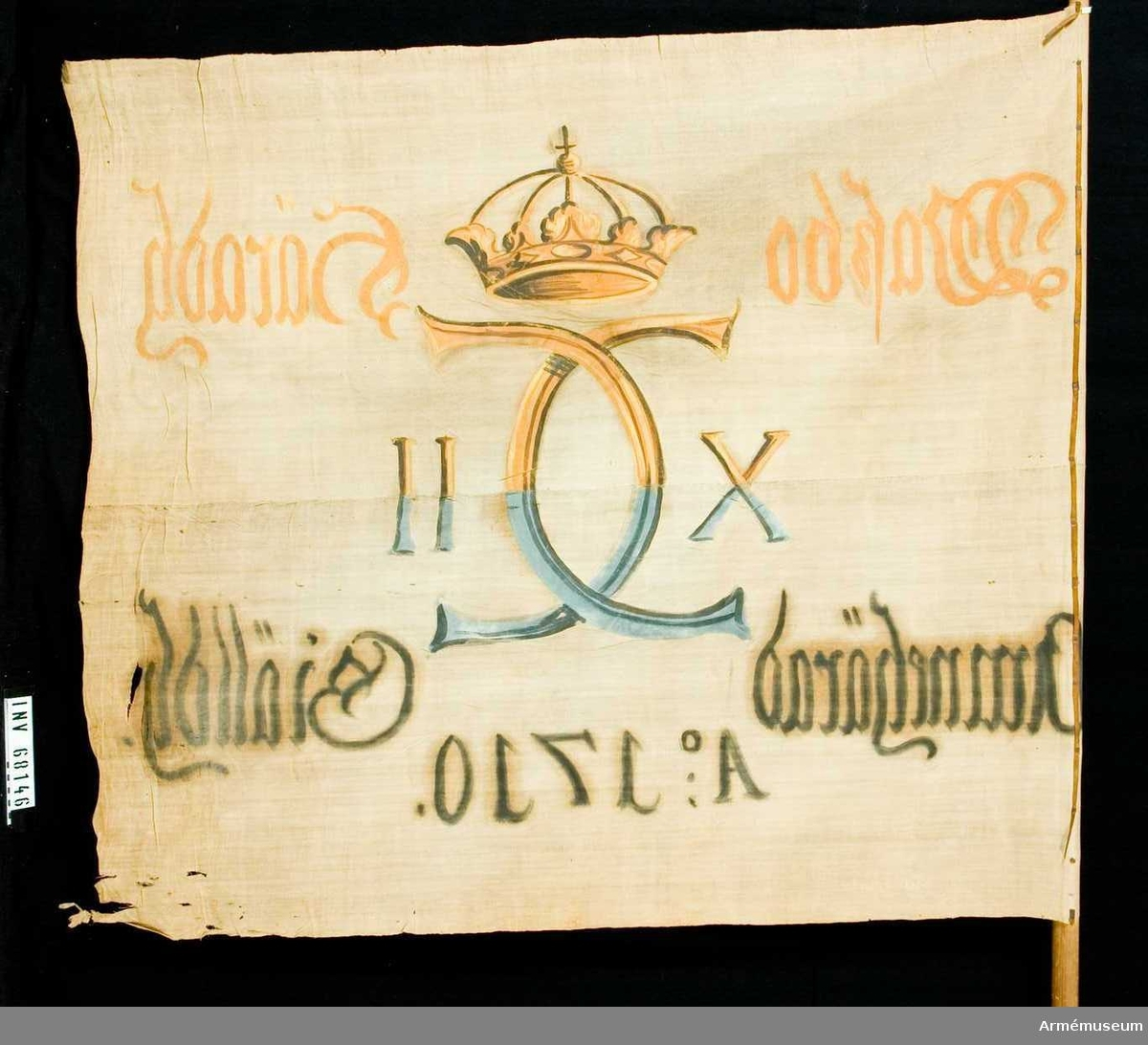 Duk: Tillverkad av enkel vit linnelärft, sammansydd av två våder. Stad i över- och underkanten, fållen lagd åt dukens utsida (i den vertikala ytterkanten). Fäst med en rad järnnagel på en liten, något defekt, skinnremsa.  Dekor: Målad i mitten, endast på dukens insida, Carl XII:s namnchiffer, krönt med sluten krona, dubbelt C. Text på ömse sidor om chiffret, upptill i gult och nedtill i svart. Under allt detta text i svart.  Stång: Tillverkad av trä. Relativt kraftig. Avfasad längst ner.