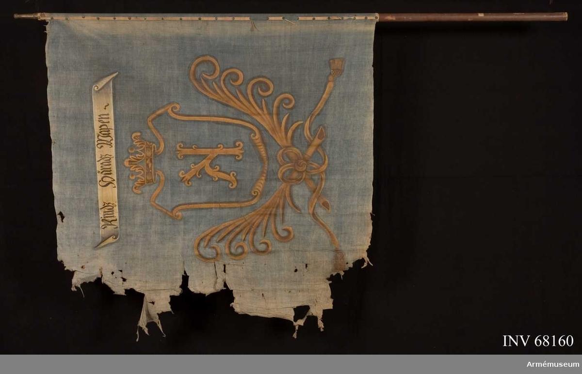 Duk: Tillverkad av enkel blå linnelärft, sydd av två horisontella våder. Dukens fåll lagd åt utsidan. Fäst vid stången med vitt kypertvävt linneband. På detta en rad mässingstennlikor.  Dekor:   Målad i mitten, lika på båda sidor, i gult en sköld krönt med öppen krona, nedtill innefattad av två korsade palmkvistar hopknutna med långa tofsprydda band, i skölden ett gult sirat K. Över vapnet ett vitt inskriptionsband med text i svart, på båda sidor om duken.  Stång: Tillverkad av trä, brunmålad. Holk av mässing.