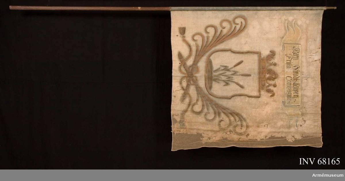Duk: Tillverkad av enkel blå (mycket blekt) linnelärft. Fållen i över- och nedre kanten lagd åt dukens utsida. Fällsöm i mitten, ca 20 mm bred. Fäst med en rad mässingstennlickor på ett gult kypertvävt band.  Dekor: Målad lika på båda sidor, i gult en med öppen krona krönt sköld. Nedtill infattad av två korsade och med långa tofsprydda band hopknutna palmkvistar i skölden tre gröna (?) strån med gula ax. Text på inskriptionsbandet på båda sidor, bandet vitt med text i svart.  Stång: tillverkad av trä, brunmålad. Något avsmalnande. Holk av mässing. Saknar spets.