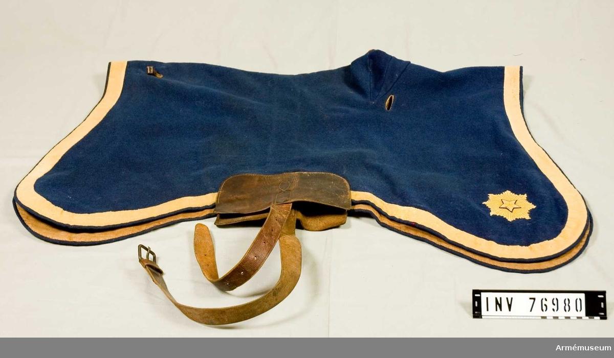 Grupp: K I. Valltrappen är gjord av blått valkat ylle med en gul list i ytterkanten, 4 cm bred, i samma tyg. Fodrad med naturfärgat linnetyg. Ingenjöremblem i de båda bakre hörnen. Mått: Längs med ryggen: 100 cm. Tvärs med ryggen: 96 cm.