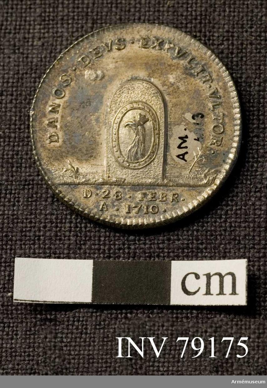 Grupp: M.  Åtsidan: CAROLVS XII D G REX SVE. Bröstbild år höger i harnesk och mantelveck, med omlindad halsduk.  Frånsidan: DANOS DEVS EXPVLIT VLTOR. En gränssten, på vilken är fästad en oval sköld, innehållande Skånes vapen, ett krönt griphuvud. I avskärningen D. 28 FEBR. A. 1710. på två rader, medaljen perlkantad.   Medaljen graverad av P. Westman. (kompl Prn)