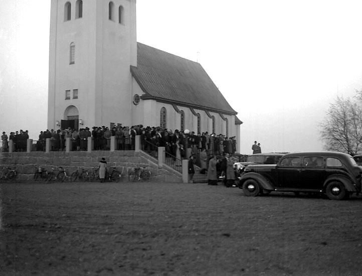 """Enligt senare noteringar: """"Bröllopsgäster och brudpar utanför kapellet.  Två bilar på parkeringsplatsen, den ena är en Volvo 801-droska."""" (BJ)"""