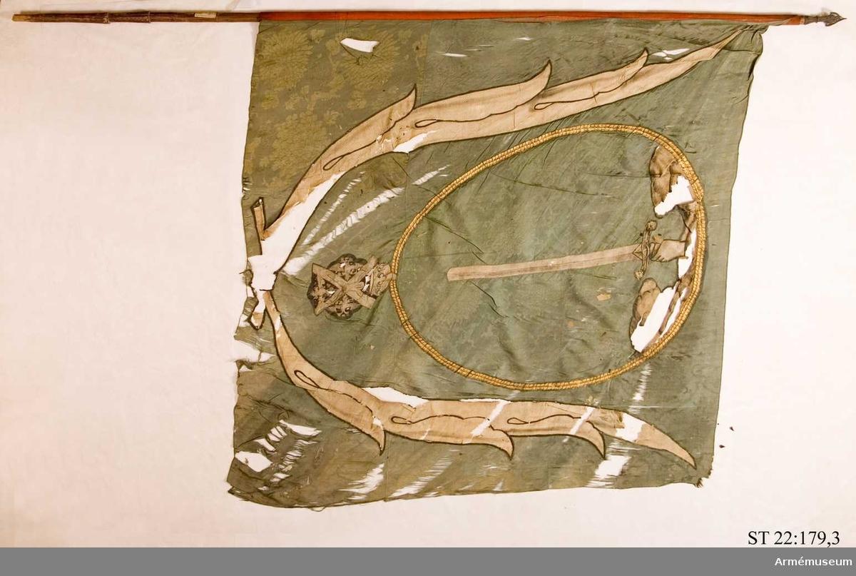 Duk av grön kinesisk sidendamast. Ur ett moln en hand hållandes ett nedåtgående svärd. Runtom den ryska St Andreas orden i målad guldkedja. Allt inramas av palmblad i vit sidenbaiberek. Målad stång med bevarad spets. På tyget ett runt stämpelavtryck.