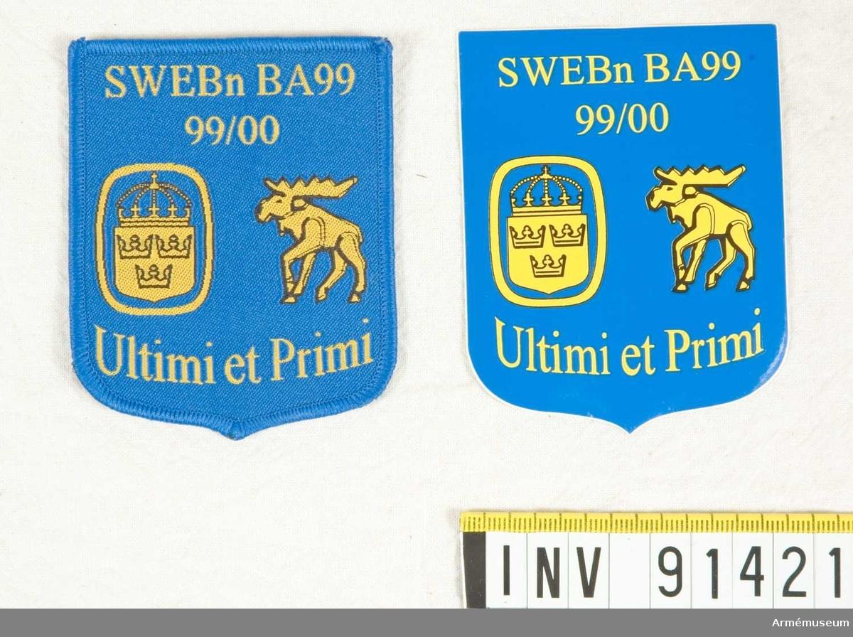 Plaketten ligger i en blå ask. 1 tyg och 1 klistermärke med samma motiv och text som åtsidan finns också.