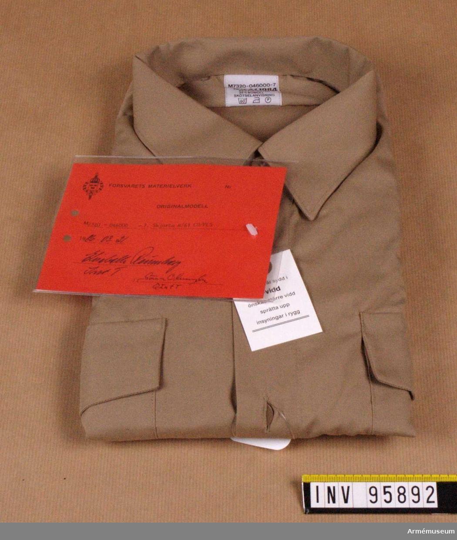 """Skjortan har hel, fast krage och ok av dubbelt tyg och motveck i ryggen samt bröstfickor med lock, som är knäppbara. Skjortan har fasta axelklaffar (42-45 mm) utan hylsor. Skjortan är avsedd för uniform m/61 (tropik) för alla försvarsgrenar. Vidhängande etikett: """"Försvarets materielverk Originalmodell M 7320-046000-7, Skjorta m/61 CO/PES, 1986-03-21 Elisabeth Rönnberg Int T / Göran Olmarker Q Int T""""."""