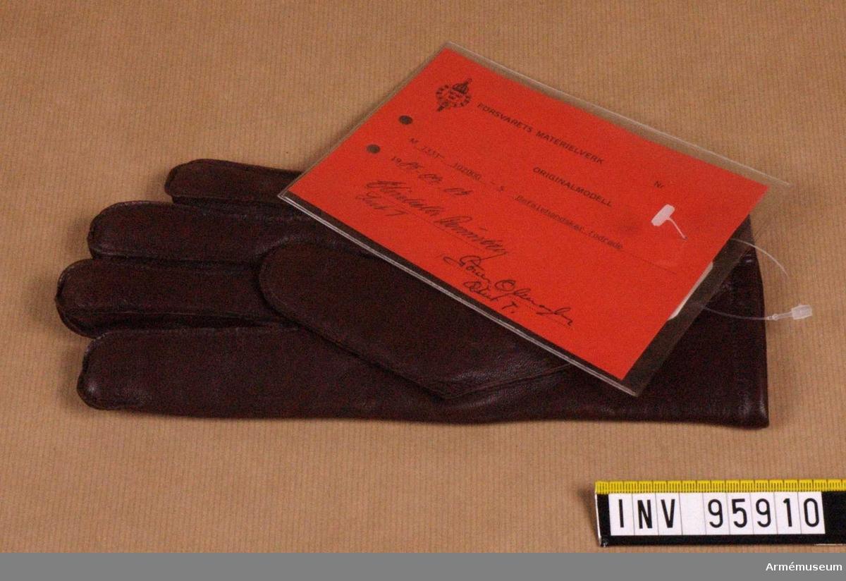 """Fodrad, femfingrad handske tillverkad av brun fårnappa och försedd med resår för åtstramning vid handloven samt slits vid överkanten. Vänsterhandske storlek 9. Vidhängande etikett: """"Försvarets materielverk, Originalmodell, M 7331-102000-5 Befälshandskar fodrade, 1985-09-04 Elisabeth Rönnberg Int T, Göran Olmarker Q Int T"""""""