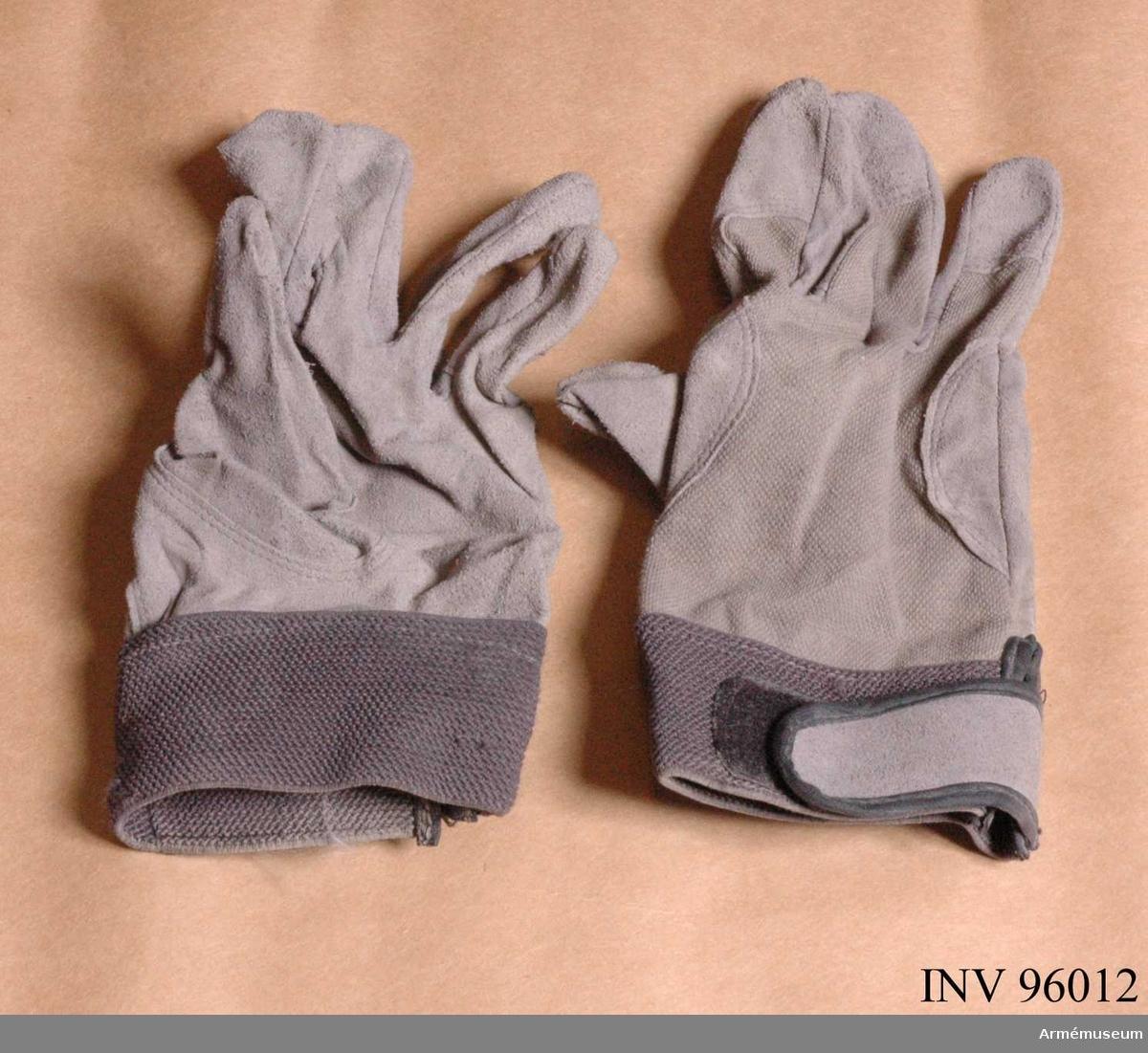 Tunna hanskar i trikå och syntetskinn. Storlek 8. Tillverkade 2008 i Kina. Ligger i väska numer två från höger i kroppsskyddet (AM.096007).