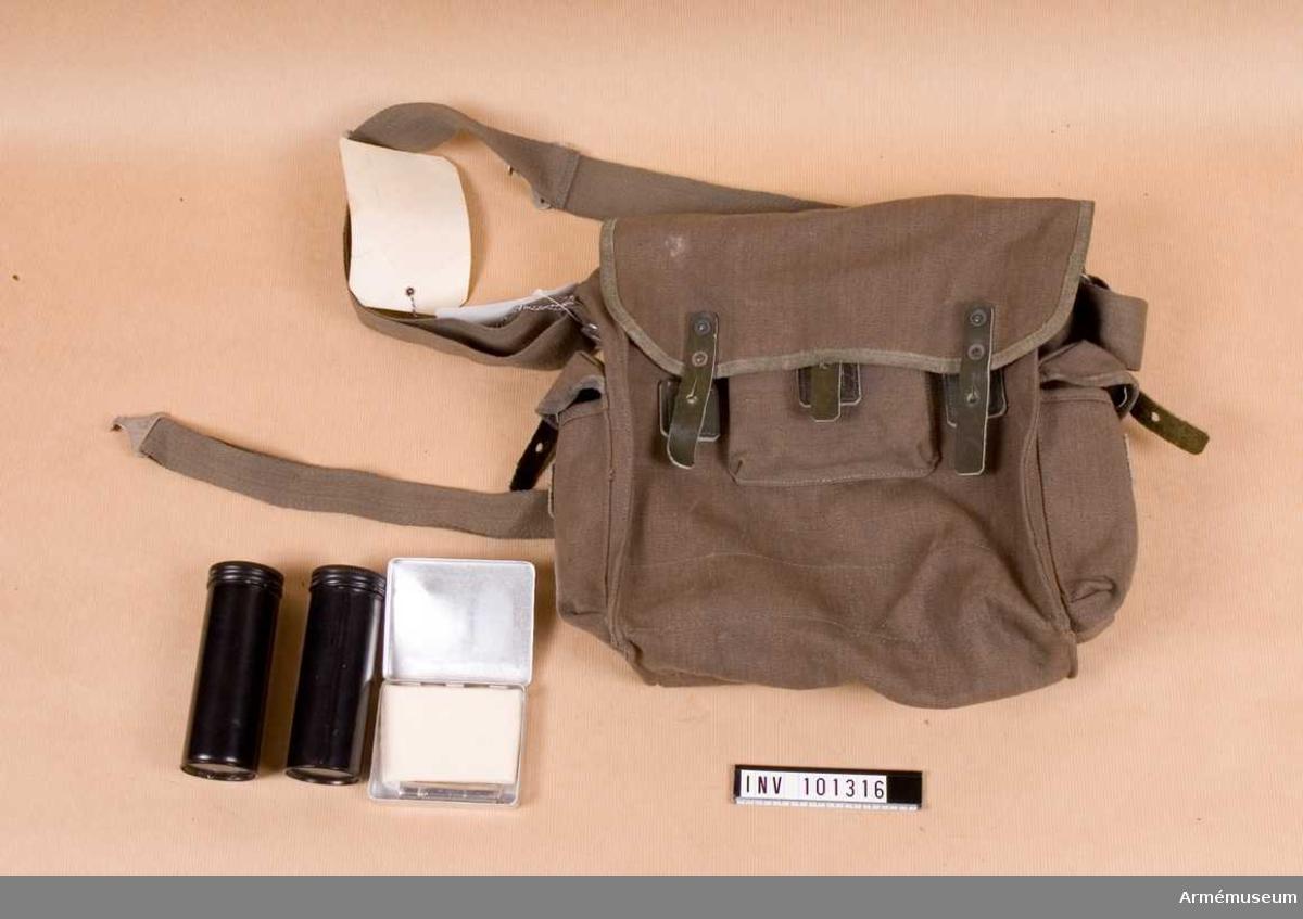 Väska av kanvas.  2 svarta dosor  i sidofacken 1 metallask med putsduk