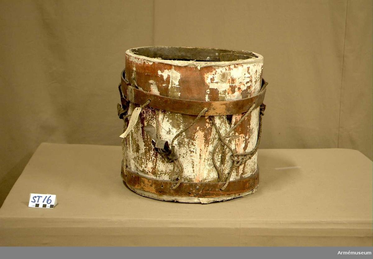 Cylindertrumma av: trä med lim och krita grunderad duk som är bemålad. Trumman är i mycket dålig kondition. Ytan är krackelerad med stort bortfall främst i de röda fälten. Duken släpper från cylindern har hål och sprickor. Metallögla som spännlinan löper igenom är fäst på insidan av cylindern med träbit och läderband.  Membran: saknas.  Veckelgjordar: finns, hänger illa på cylindern med hjälp av delar från spännlina. Båda äro lindade med smala läderband.    Spännlina: är ej komplett. Det finns två spännstroppar.  Spännringar: saknas.  Utsmyckning: röda kilar målade på gul botten. Mönstret är ristat i grunden.  Märkning : hängandes pappersetikett  Lewenhauptska  No 16  östra.