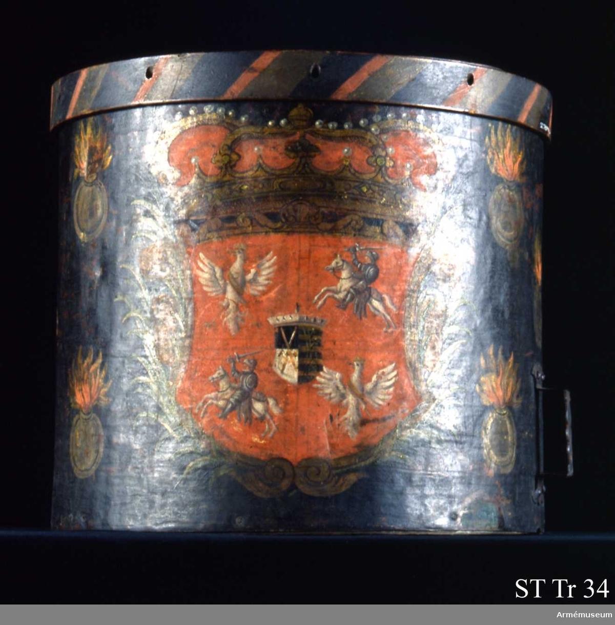 Cylindern dekorerad med en krönt vapensköld med det polsk-litauiska riksvapnet samt det sachsiska vapnet i hjärtskölden omgivet av palmkvistar och rykande granater. Av inslagna punkter och romerska siffror vid cylinderns skarv och veckelgjordar framgår det att trumman ingår i en serie om ursprungligen sex stycken varav denna är nummer VI. Membraner saknas. Cylinder av koppar, veckelgjordar av trä, sejarhållare (handtag) av järn.