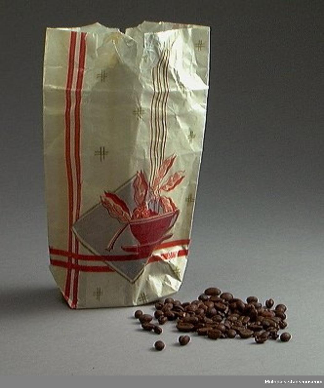 """Påse innehållande malet kaffe, ½ kg, av glansigt papper med rutmönster och kronor i gult mot roströd bakgrund. Nederst är påsen gul- och vitrandig, med beteckningen """"Kaffe"""" i skrivstil i rostrött mot benvitt, inramat emblem. På sidorna runt emblemet: """"Ica, ansluten till Köpmännens Inköpscentral"""". På andra sidan: """"Forsberg & Grahns Kronmocca, tel 169, Lönsboda"""" i brunt mot benvitt, inramat emblem."""