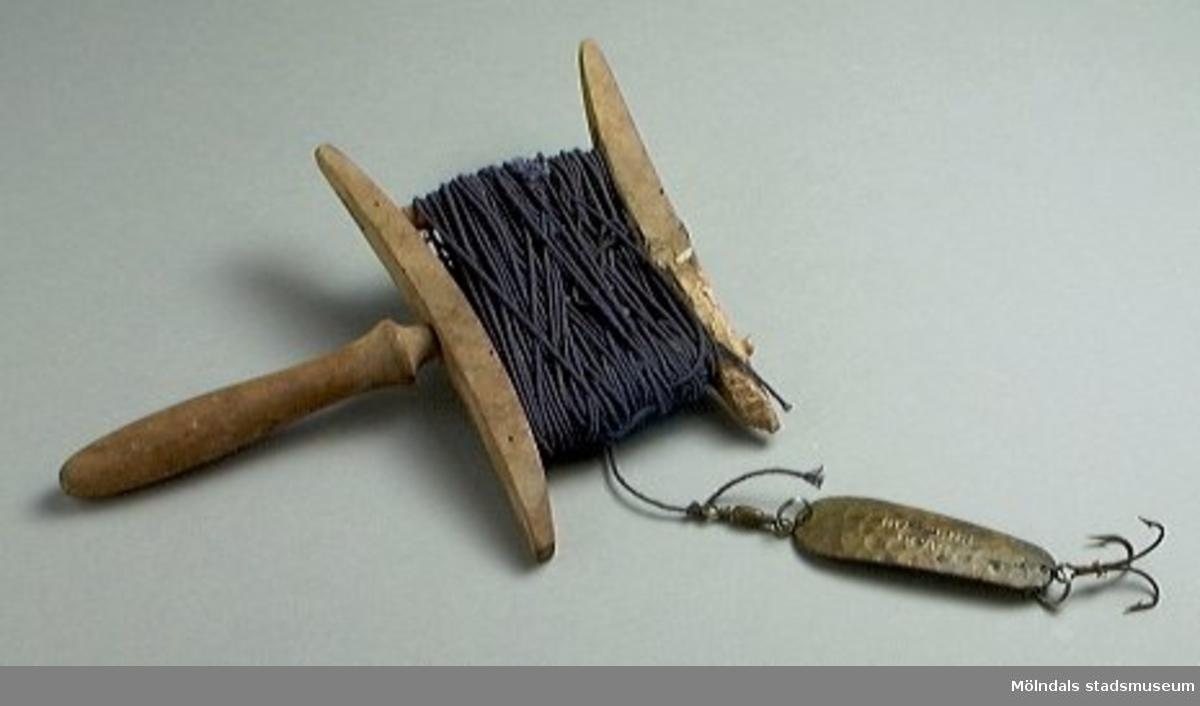 """Rulle av trä med blå bomullstråd. Drag med krok. Draget märkt """"Gubbens drag"""". Rullen skavd.Ägaren var morfar till givarens fru."""