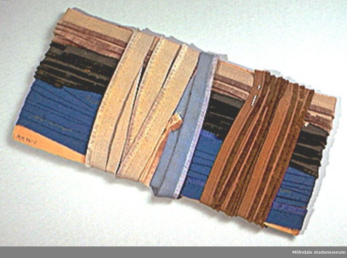 På vissa bands baksida påtryckt kvalitetsnamn. Av givaren inköpt på auktion.Tretton band med frans i olika längd och färg uppvirade på två pappskivor och hophållna med knappnålar.