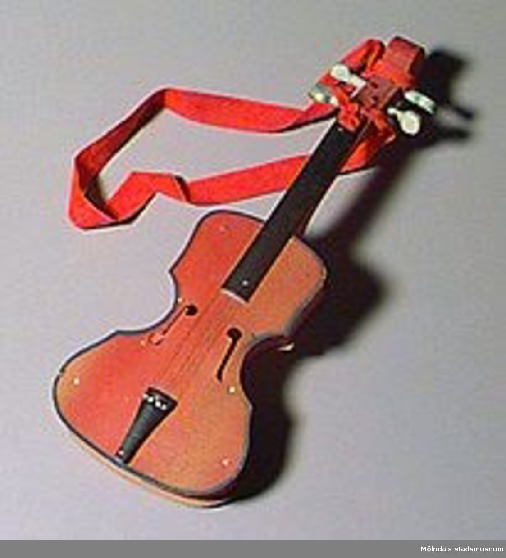 Leksaksgitarr. Ett rött band är fästat vid handtaget. (För barnteater?).Ytterligare material: metall, textil.