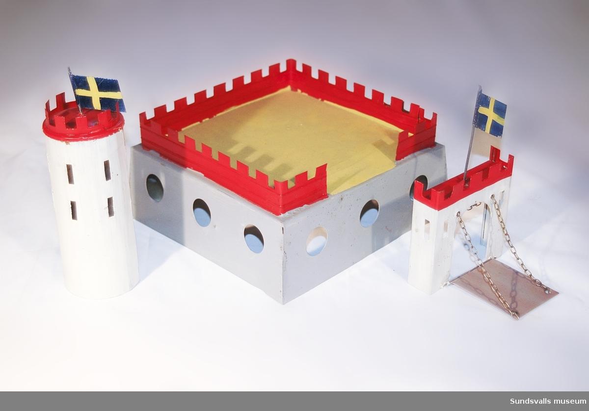 Leksaksfästning med ett löstagbart torn och port. Över dessa vajar två svenska flaggor.