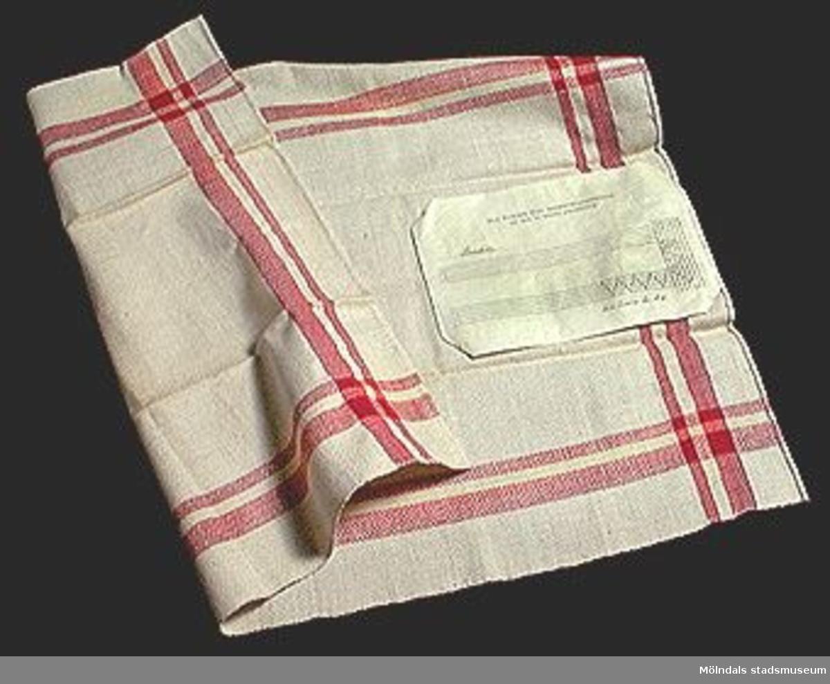 """Naturvit handduk med röda ränder i sidorna. På baksidan sitter en lapp med vävschema.Elevarbete från textillärarseminariet.Tekniken korndräll är ett sk bindningsmönster (för att åstadkomma mönster i väven genom förändring i vävens textur). Bindningsmönstret kan i sin tur kan indelas i 4 olika grupper. Korndräll tillhör den första gruppen som kallas kypert. (Se """"Ur textilkonstens historia"""" av Agnes Geijer s.70).Tidigare sakord: handduk med vävschema.Gåvan förmedlad genom Gustav Wickström."""