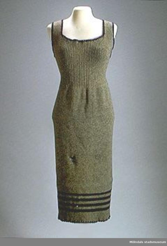 Stickad hängselklänning med ribbstickat ok och slätstickad kjol. Hängslena knäpps med tre knappar. Grå med blå ränder nertill och blå virkade kanter runt. Maläten.