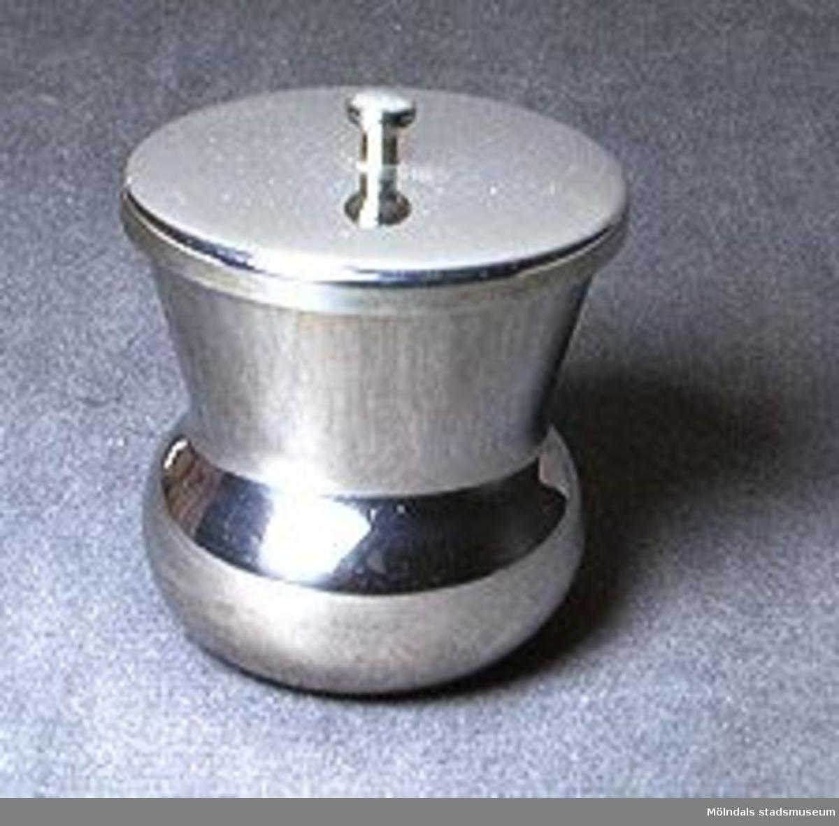 Krukformad kopp i rostfritt stål med ett runt lock, som har försätts med en liten knopp.Stämpelmärkt i botten med: KOCKUMS Rostfria.Tidigare sakord: kopp med lock.Tidigare specialbenämning: spottkopp.