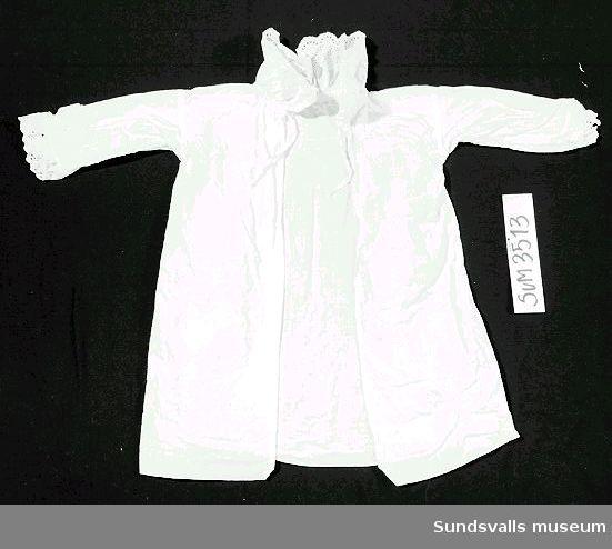 Barnskjorta av vit bomull med spetskrage och spets kring ärmarna.