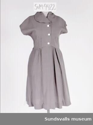 Klarblå klänning. Knäppning med tre vita knappar på livet, rundad krage och holkärmar. Kjolen är något veckad i midjan och klockad. I fållen är en lapp fastnitad med texten 'Strömbo Tidaholm Barnkonfektion, pris 34 kr...' etc.