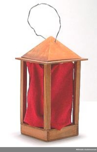 Leksakslykta, liknar en stallykta med rött tyg istället för glas. Batteridriven. Ingår i en samling från Holtermanska daghemsverksamheten.