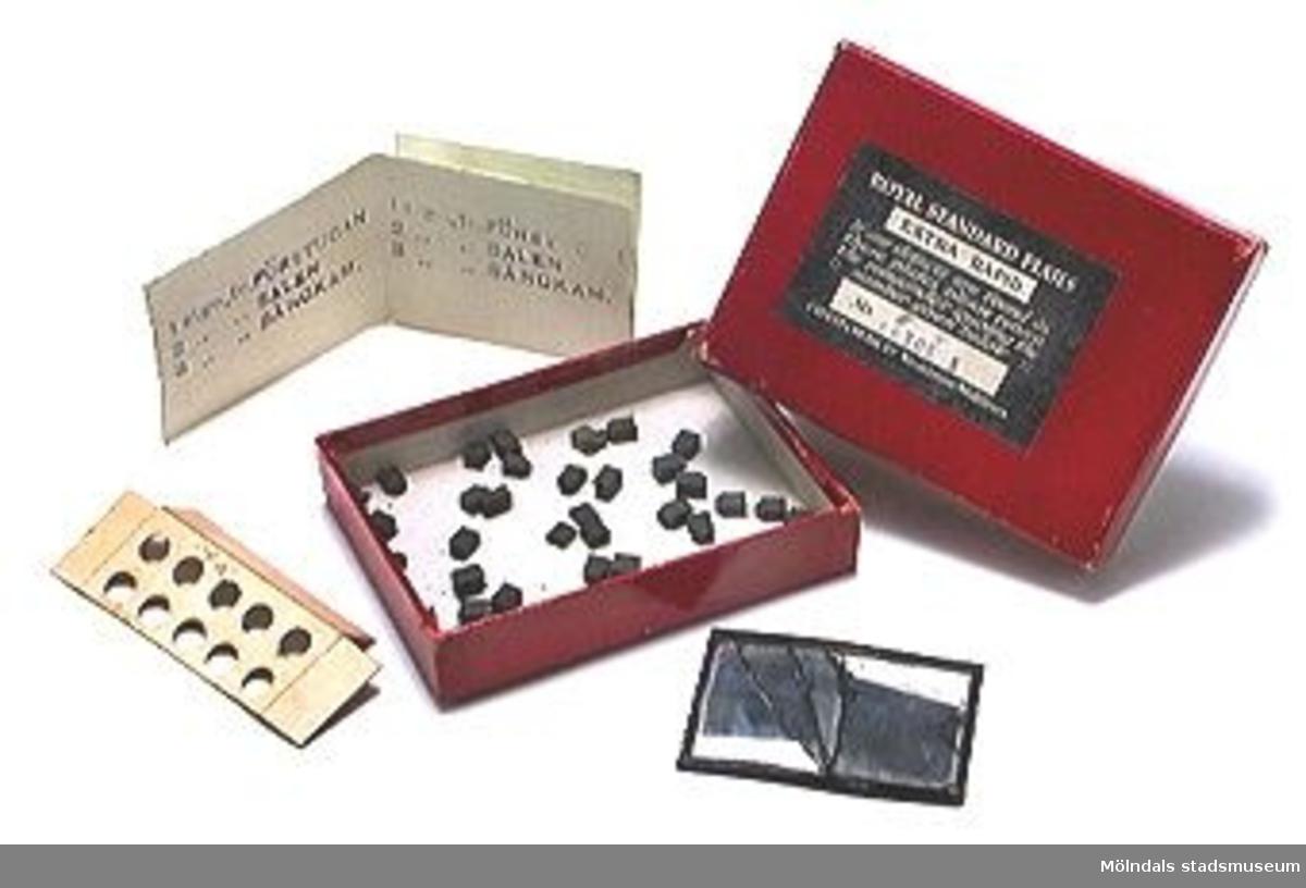 Stämpeldynor för tryckning av bokstäver på papper, i en ask ligger stämpeldynor och en spegel.