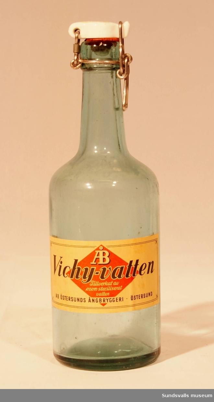 Flaska i gröntonat glas med patentkork från AB  Östersunds Ångbryggeri. Etikett med texten 'ÅB Vichy-vatten, Tillverkat av ozon-steriliserat vatten, AB ÖSTERSUNDS ÅNGBRYGGERI, ÖSTERSUND'.